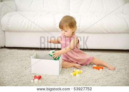 Little girl in dress puts toys in box near white sofa at home. Shallow depth of field.