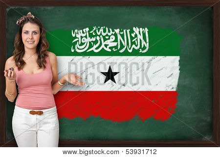Beautiful And Smiling Woman Showing Flag Of Somaliland On Blackboard