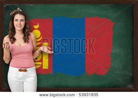 Beautiful And Smiling Woman Showing Flag Of Mongolia On Blackboard