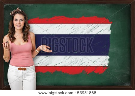 Beautiful And Smiling Woman Showing Flag Of Thailand On Blackboard