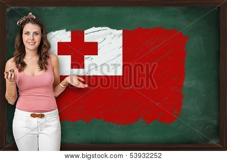 Beautiful And Smiling Woman Showing Flag Of Tonga On Blackboard