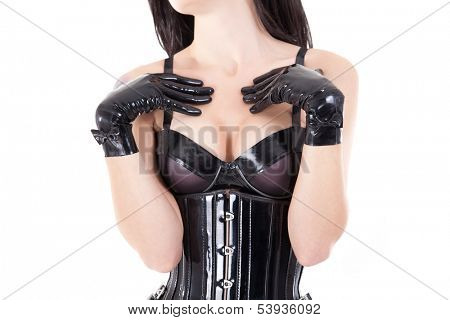Close-up shot of female breast in latex bra, isolated on white background