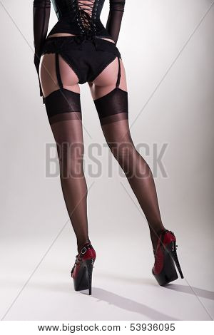 Beautiful long legs in vintage nylon stockings and high heels, studio shot on white background