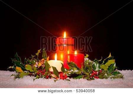 Christmas still life of three candles on snow surrounded by a fresh green holly, ivy and spruce garland against a black background.