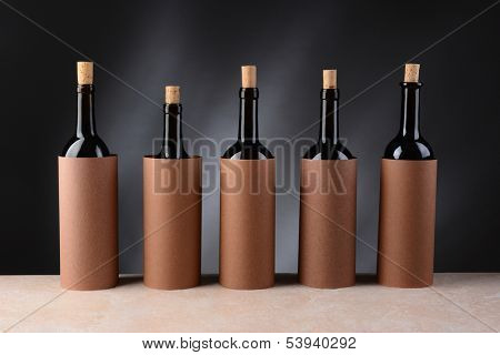 Five different wine bottles set up for a blind wine tasting. The bottles have the corks partially removed and are covered by blank cylinders to hide the label. Horizontal format.