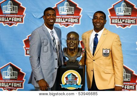 CANTON, OH-AUG 3: Duron Carter (L) and father and former receiver Cris Carter pose with his bust at the NFL Class of 2013 Enshrinement Ceremony at Fawcett Stadium on August 3, 2013 in Canton, Ohio.