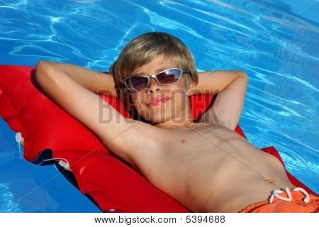 Relaxed Boy On Air Mattress With Sun Glasses