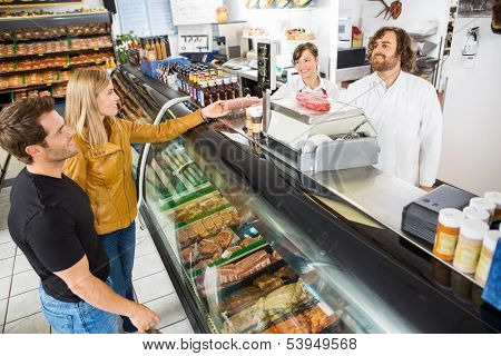 Couple purchasing meat from salesman at counter in butcher's shop