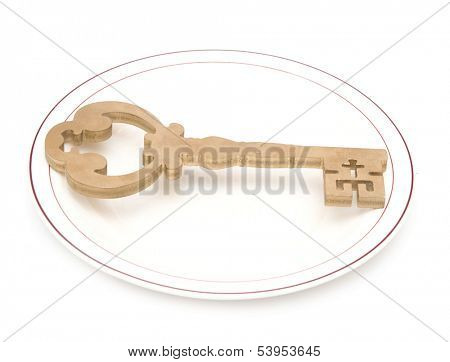 Big vintage key on white china plate with golden edging isolated on white background