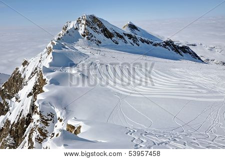 Snowy mountain landscape in sunny weather with ski piste