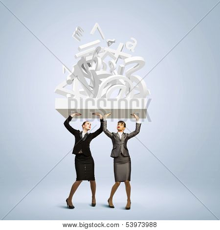 Image of two businesswomen holding burden above head