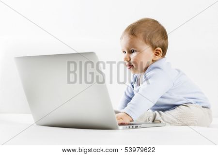 Young IT specialist - Adorable baby boy sitting on couch and looking with interest at laptop screen, on white background.