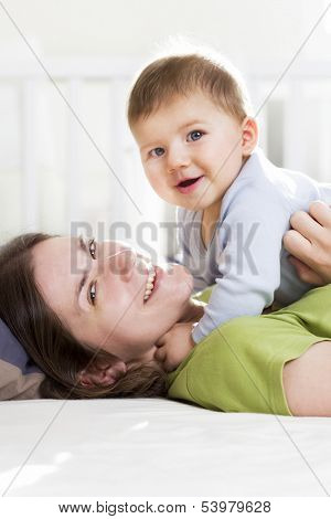 Happy family: Joyful mother and baby boy lying down in bed, laughing and having fun while she is tickling him.