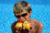 Smiling Boy With Sun Glasses At Swimming Pool With Two Apples