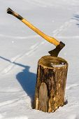 stock photo of ax  - Ax stuck in wood log snow winter - JPG