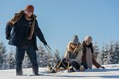 stock photo of luge  - Young people enjoy sunny winter day sledge man pulling girlfriends - JPG