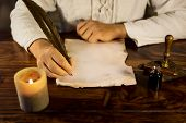 picture of inkpot  - a man writing on a old parchment