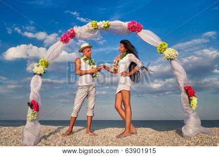 Groom with bride wearing lei, dancing under archway on beach