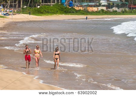 WELIGAMA, SRI LANKA - MARCH 7, 2014: Young tourists walking on sandy beach. Tourism and fishing are two main business in this town.