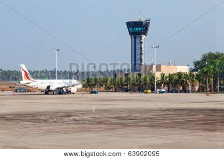 COLOMBO, SRI LANKA - FEBRUARY 19, 2014: Airplane parked on apron in front of air traffic control tower at Bandaranaike International Airport. It is hub of Sri Lankan Airlines, the national carrier.