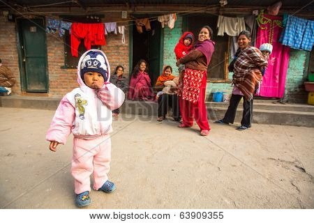 KATHMANDU, NEPAL - DEC 19, 2013: Unidentified local children near their homes in a poor area of the city. The caste system is still intact today but the rules are not as rigid as they were in the past