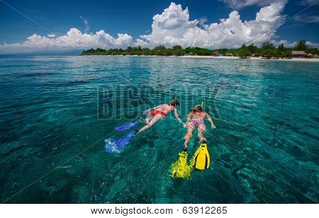 Two ladies snorkeling in tropical clear sea near the green island at sunny day. Gili Trawangan island, Indonesia