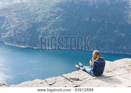 Woman sitting on Pulpit Rock / Preikestolen, Norway