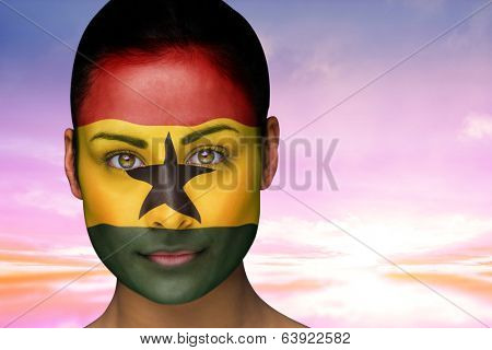 Composite image of beautiful brunette in ghana facepaint against beautiful blue and yellow sky