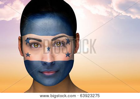 Composite image of beautiful brunette in honduras facepaint against beautiful orange and blue sky