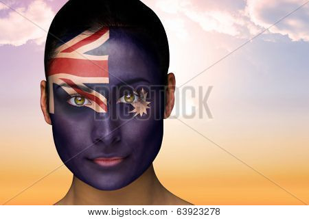 Composite image of beautiful brunette in australia facepaint against beautiful orange and blue sky