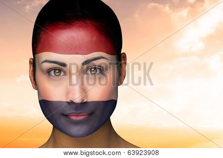 Composite image of beautiful brunette in netherlands facepaint against beautiful orange and blue sky