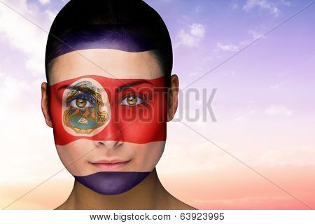 Composite image of beautiful brunette in costa rica facepaint against beautiful orange and blue sky