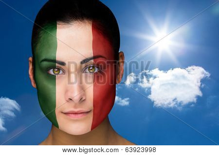 Composite image of beautiful brunette in italy facepaint against bright blue sky with clouds