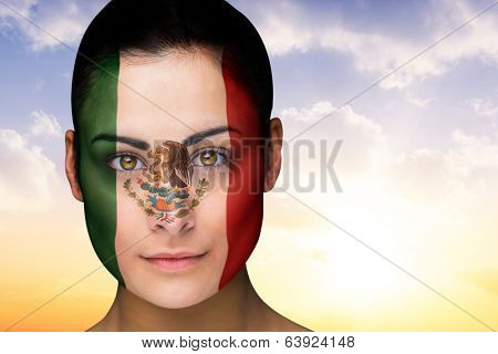 Composite image of beautiful brunette in mexico facepaint against beautiful orange and blue sky