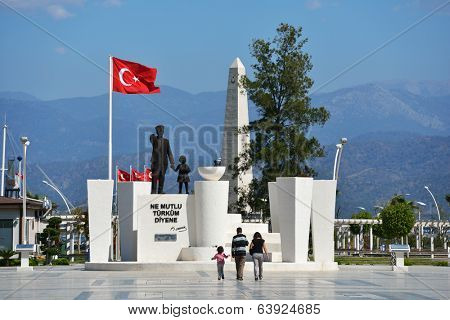 FETHIYE, TURKEY - APRIL 1, 2014: People go toward the monument to Ataturk. The founder of Republic of Turkey still is esteemed in the country today