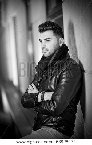 Top view of handsome male model in leather jacket posing thinking. Cool and trendy young man