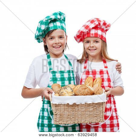 Happy kids with chef hats holding basket with fresh bakery products - isolated