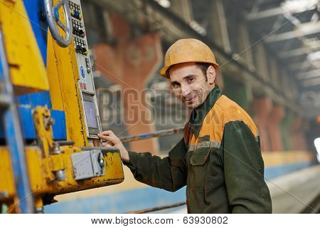 industrial worker operating concrete machine at factory workshop