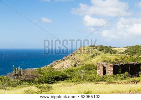Old Building On Green Hill Over Blue Sea