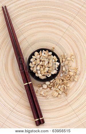 Ginseng root herb with chopsticks on a circular wooden bowl. Ren shen.