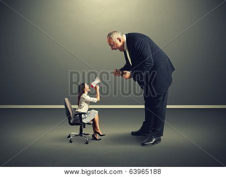 dissatisfied small woman screaming at big angry man over dark background