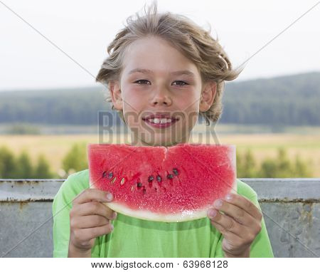 boy eats a piece of watermelon