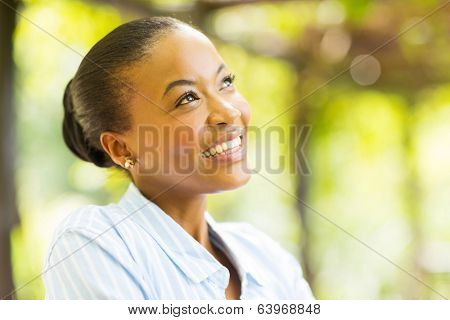 cute young african woman daydreaming