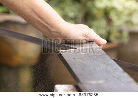 Carpenter Worker Sawing Wood Board With Hand Saw