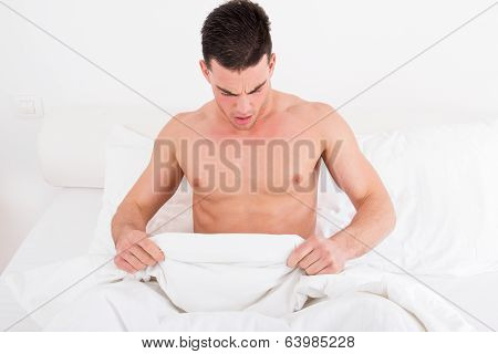 Half Naked Young Man In Bed  Looking Down At His Underwear