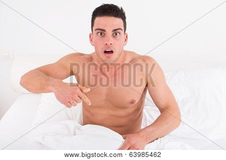Half Naked Young Man In Bed  Looking Down At His Underwear At His Penis
