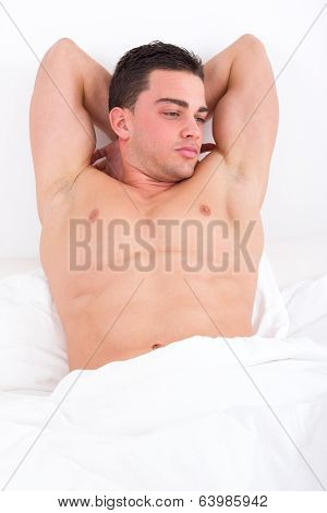 Seductive Pensive Man Lying In Bed With Naked Torso