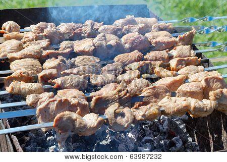 Meat is roasted on skewers in smoke