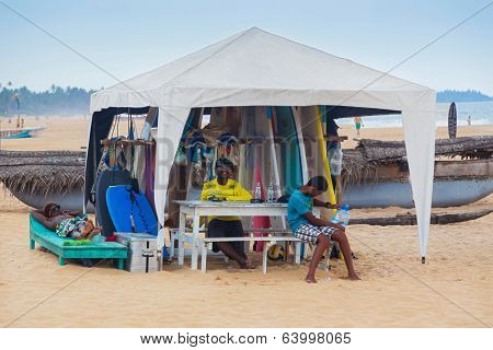 HIKKADUWA, SRI LANKA - FEBRUARY 20, 2014: Local men renting surf boards at Weligama beach, a well-known international destination for board-surfing.