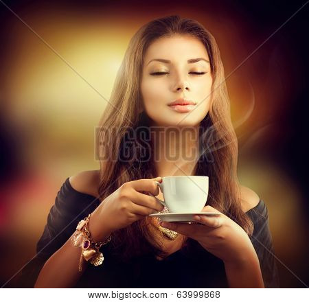Coffee. Beautiful Woman Drinking Tea or Coffee in Cafe. Beauty Model Girl with the Cup of Hot Beverage. Warm Colors Toned